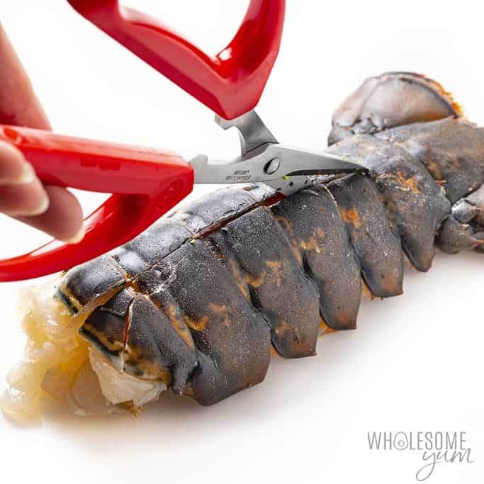 Using kitchen shears to cut lobster tail