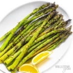 Grilled asparagus spears on a plate with lemon wedges