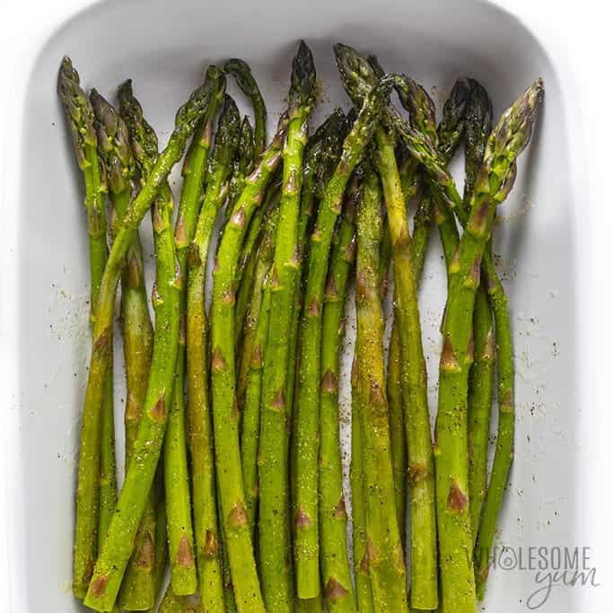 Oiled and seasoned asparagus in a dish