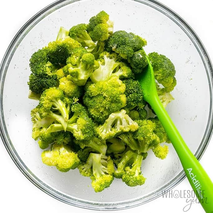 Raw broccoli with oil and seasonings in a bowl
