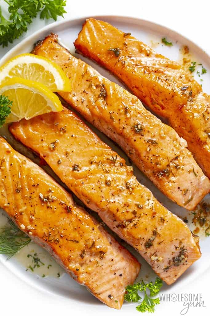 4 pan fried salmon fillets on a plate