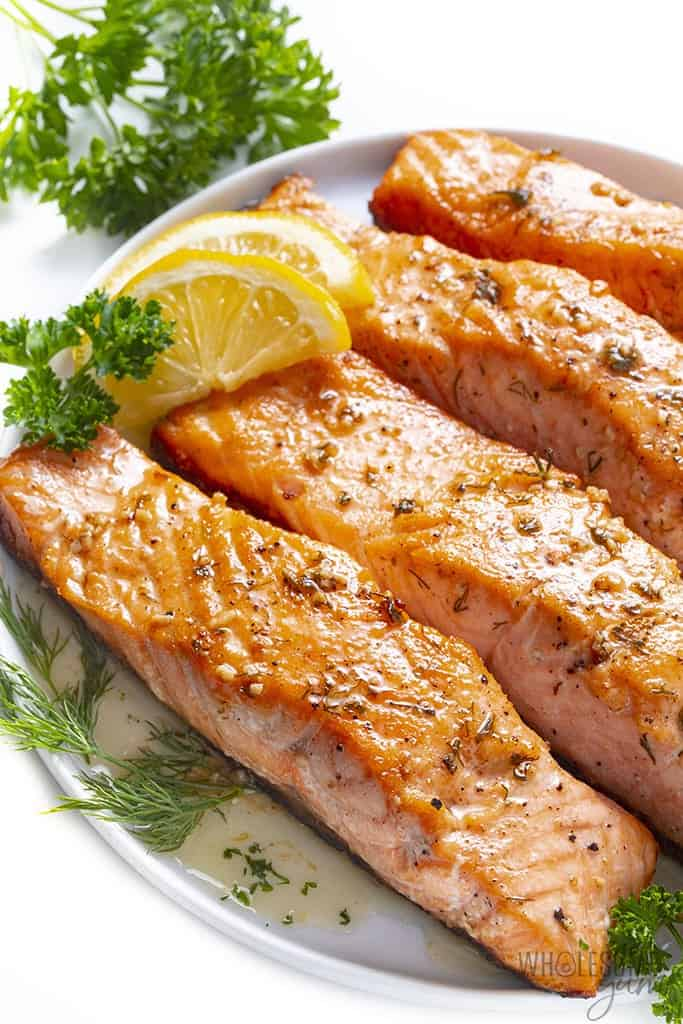 Plate with pan seared salmon and lemon wedges