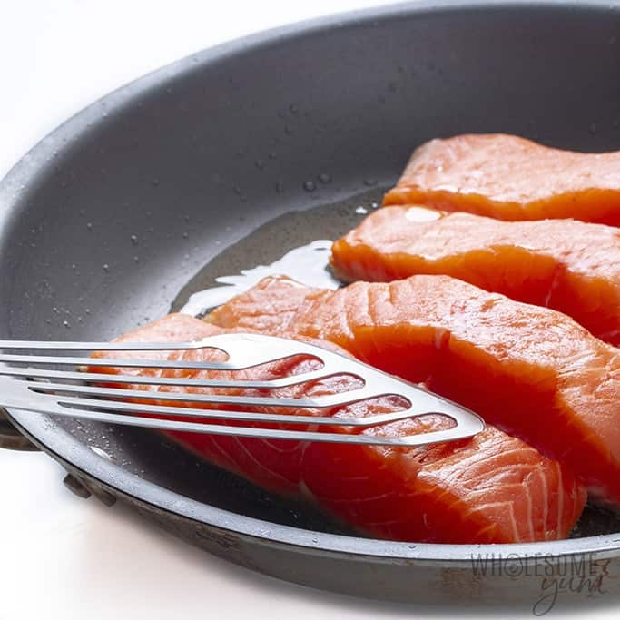 Frying salmon with fish spatula holding fish down