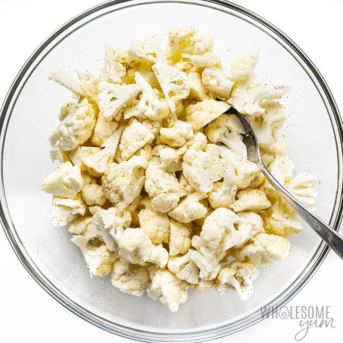 Raw cauliflower florets in a bowl with oil and seasoning