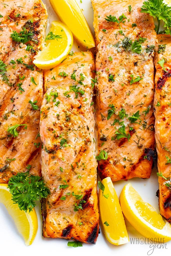 Grilled salmon fillet with lemon wedges and parsley