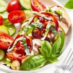 Piece of chicken Caprese on a plate with fresh basil