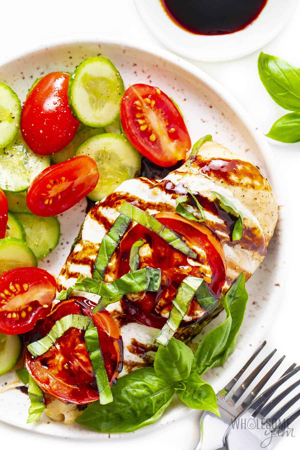 Chicken Caprese on a plate with fresh basil
