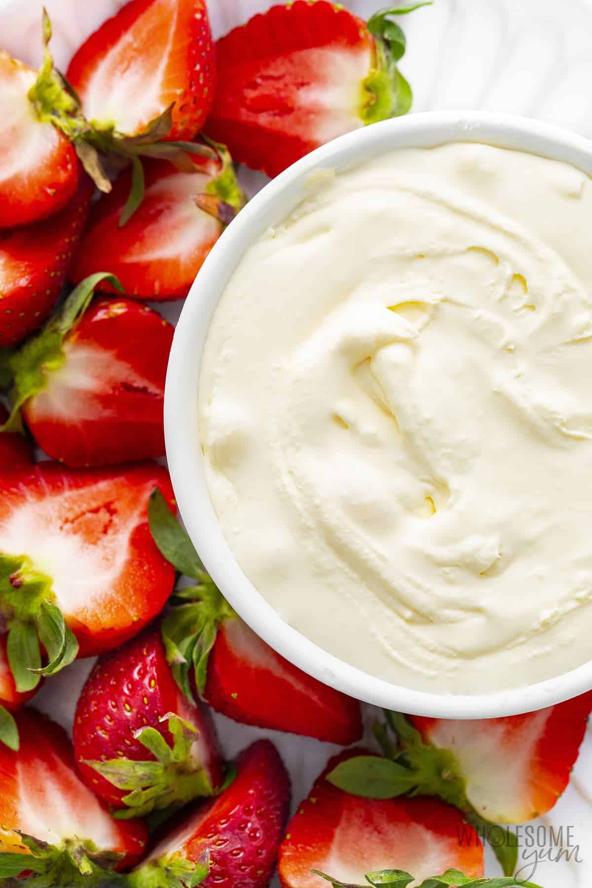 Mascarpone cheese in a bowl next to a plate of strawberries