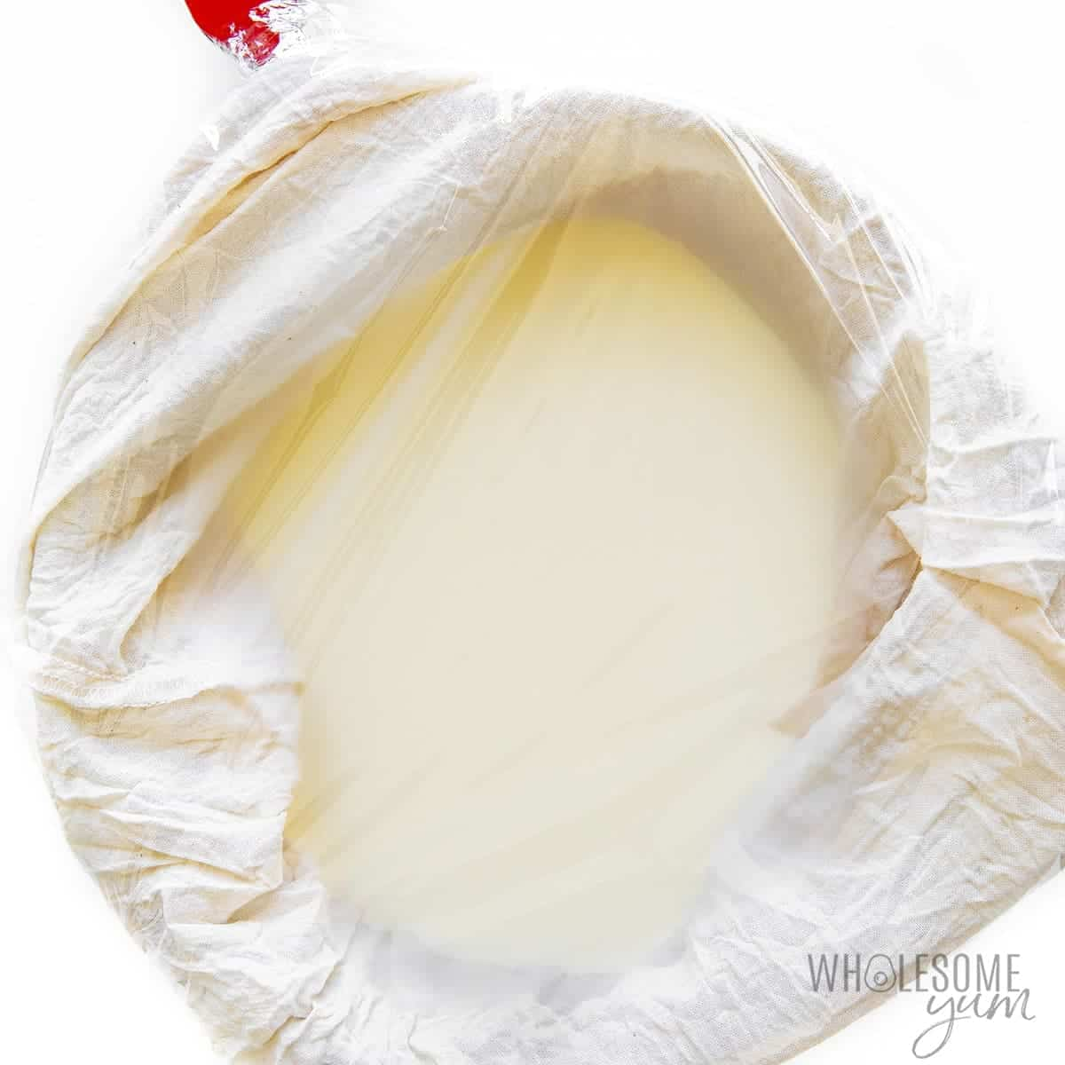 Mascarpone base over cheesecloth, covered in plastic wrap