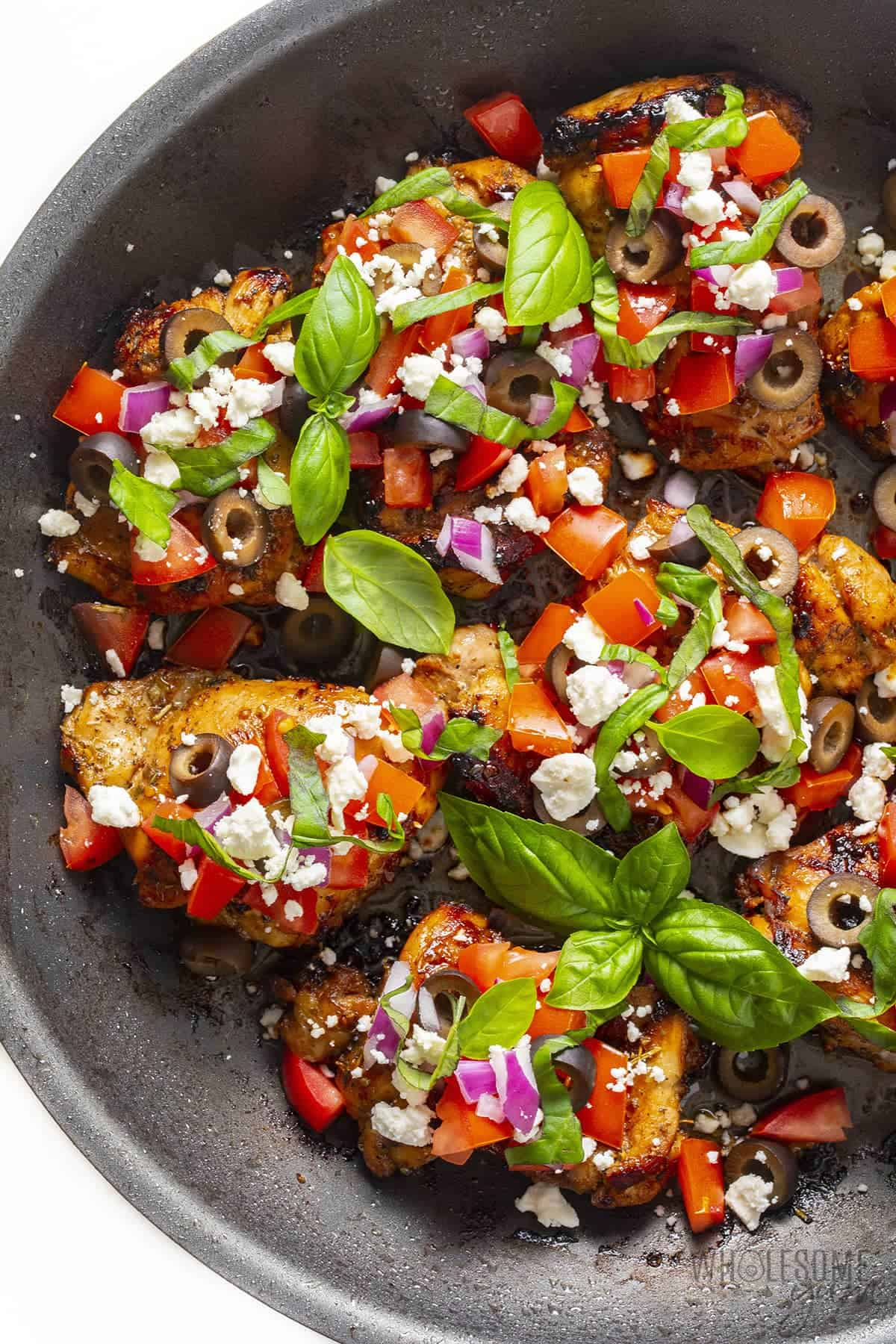 Mediterranean chicken thighs with toppings in a pan