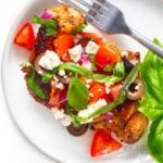 Mediterranean chicken on a plate with fresh basil
