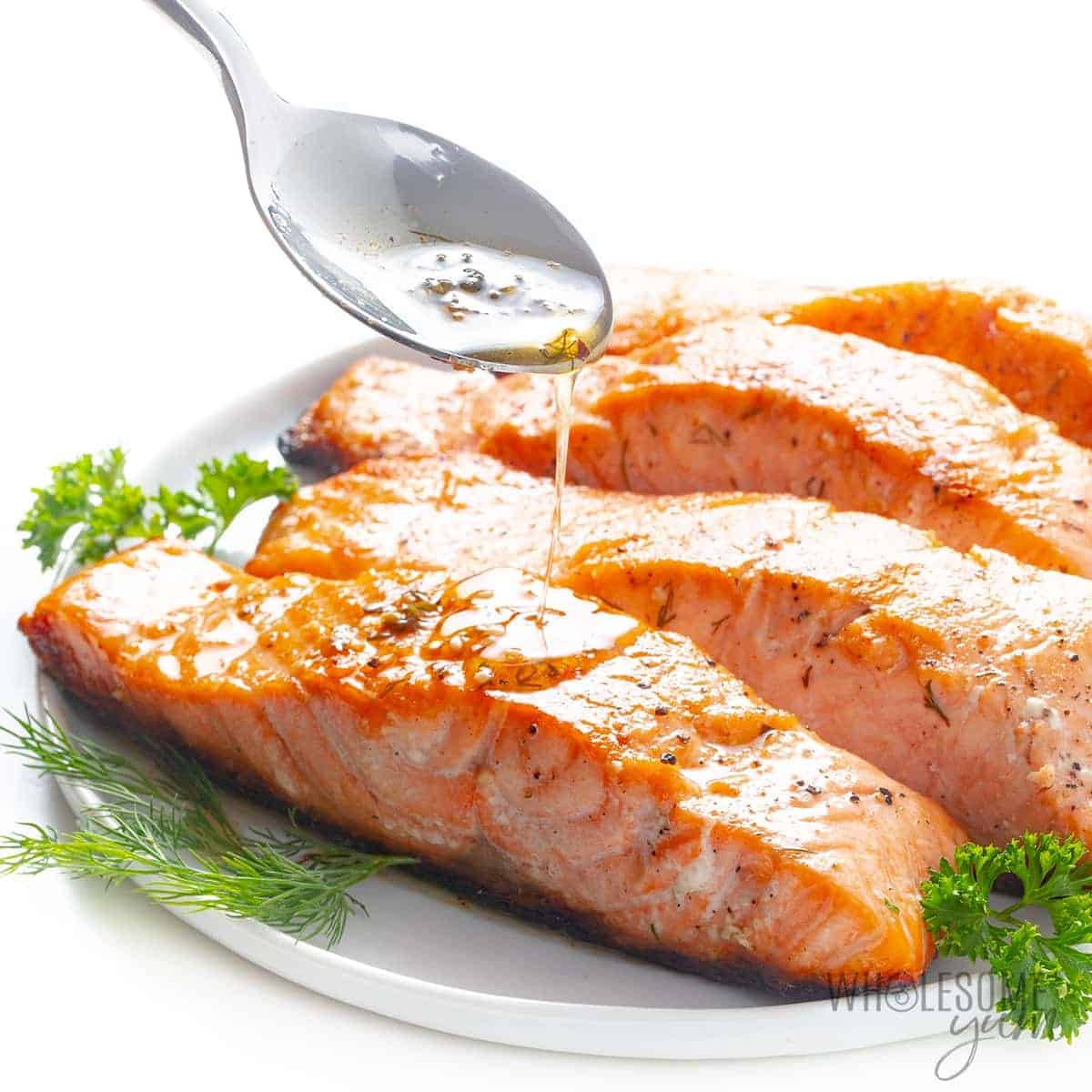 Pan seared salmon with lemon butter sauce drizzled with a spoon
