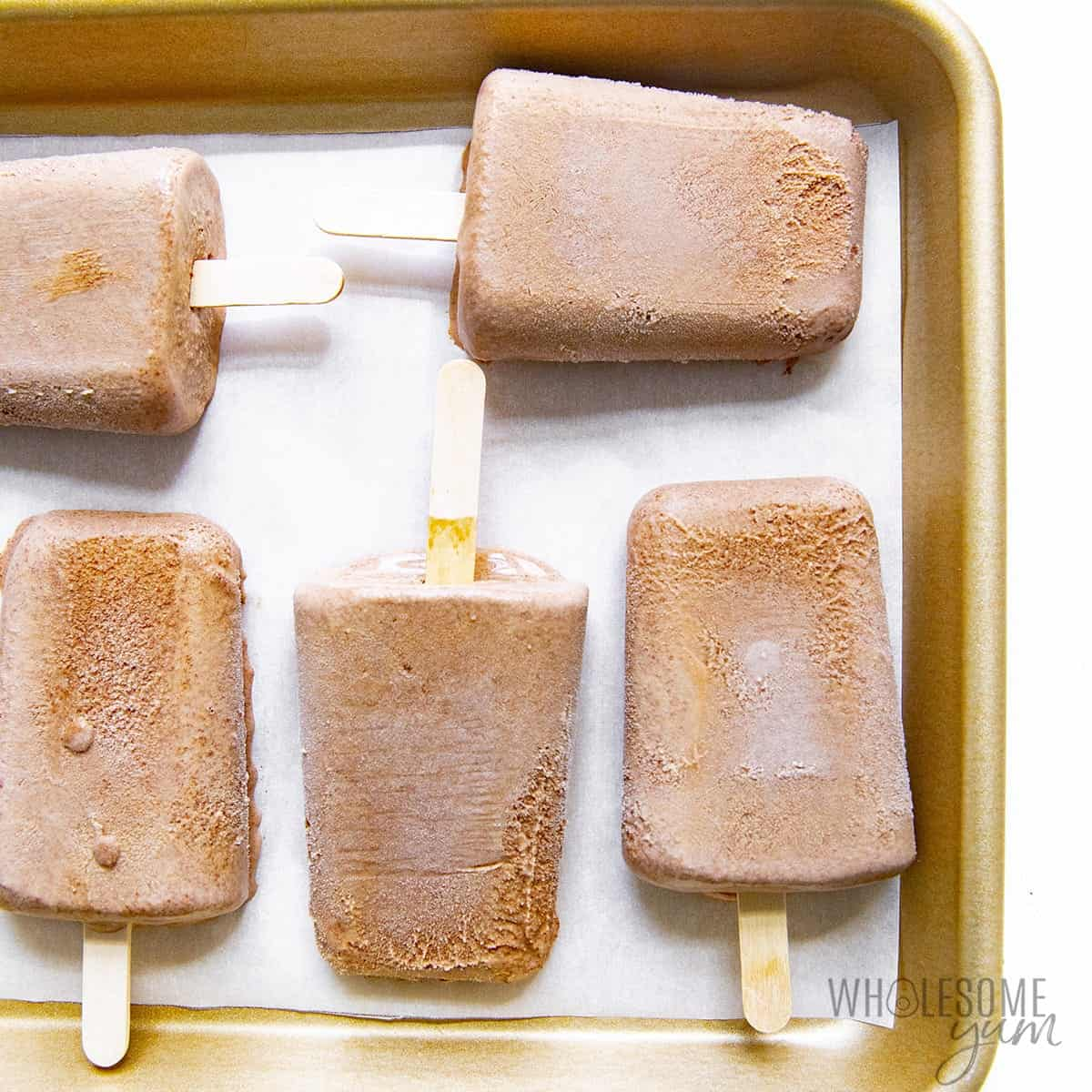Healthy homemade fudgesicles sitting on a pan to freeze for later