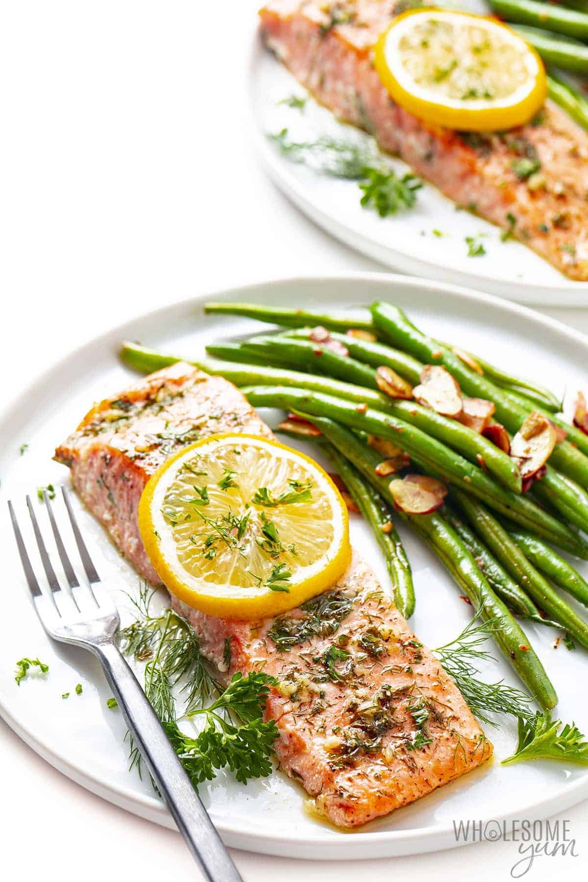 Oven baked salmon with green beans on plates
