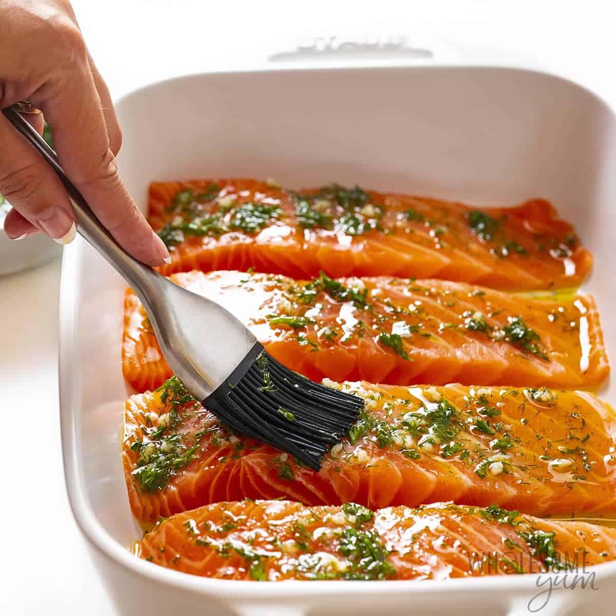 Brushing olive oil mixture on salmon