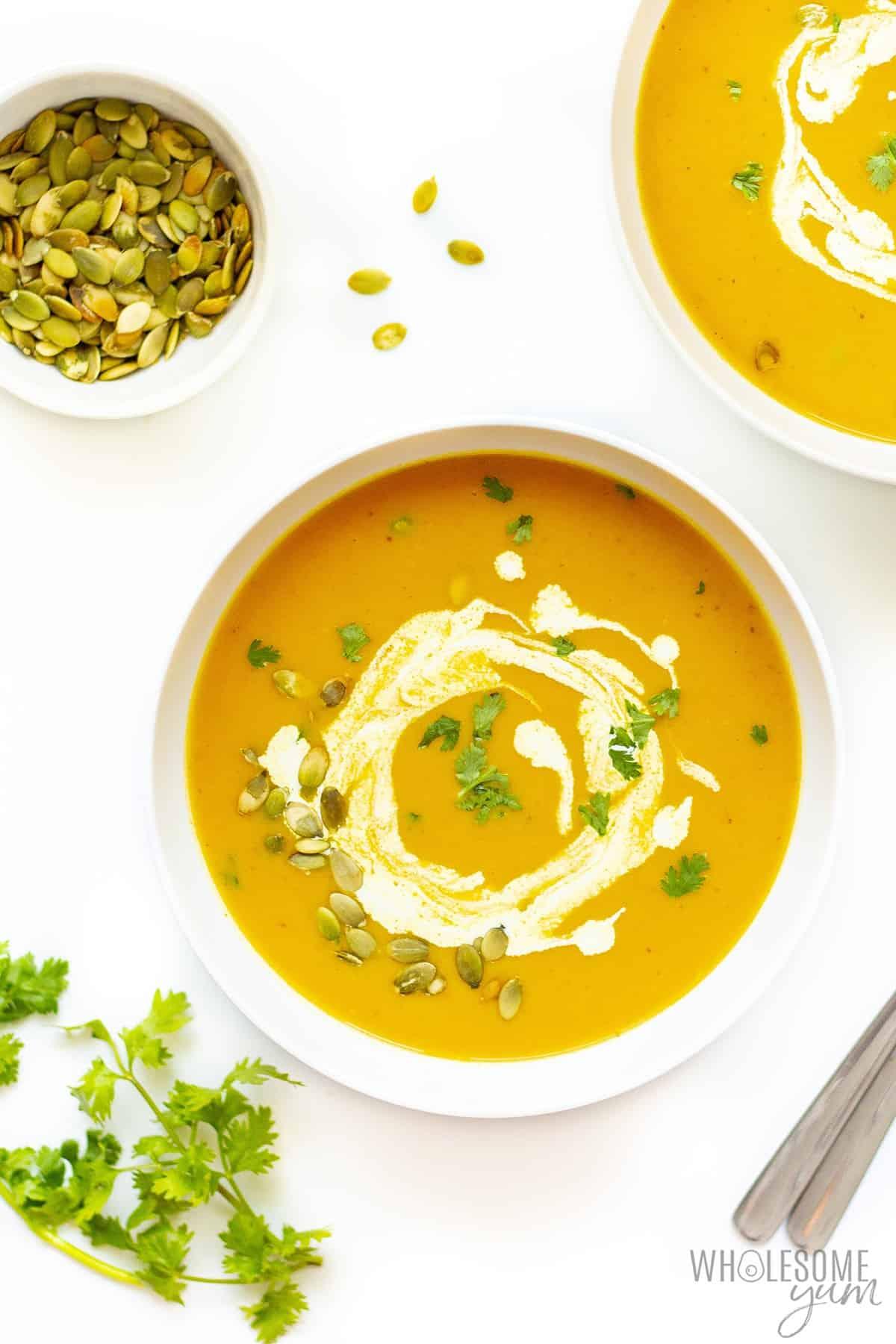 Bowls of pumpkin soup with garnish