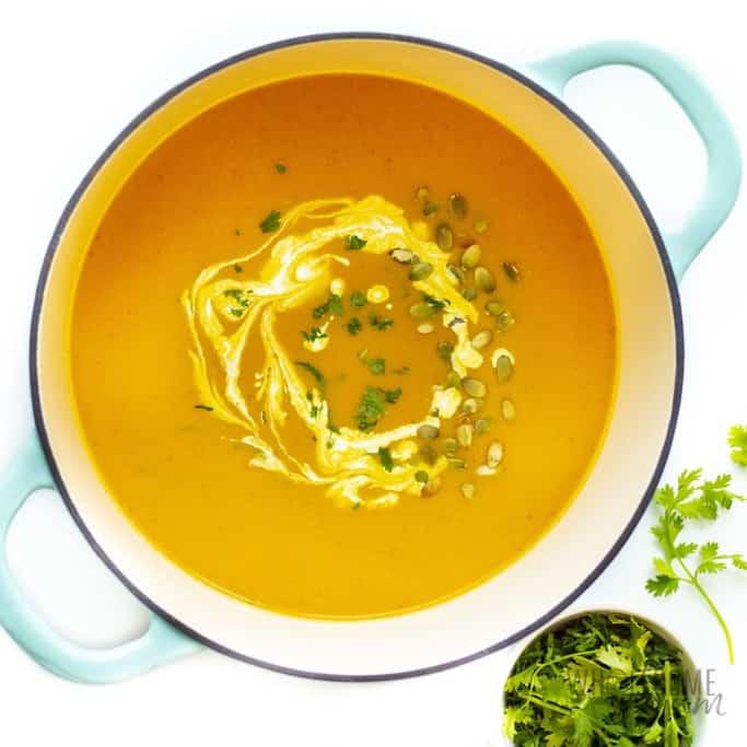 Creamy pumpkin soup with garnish in dutch oven