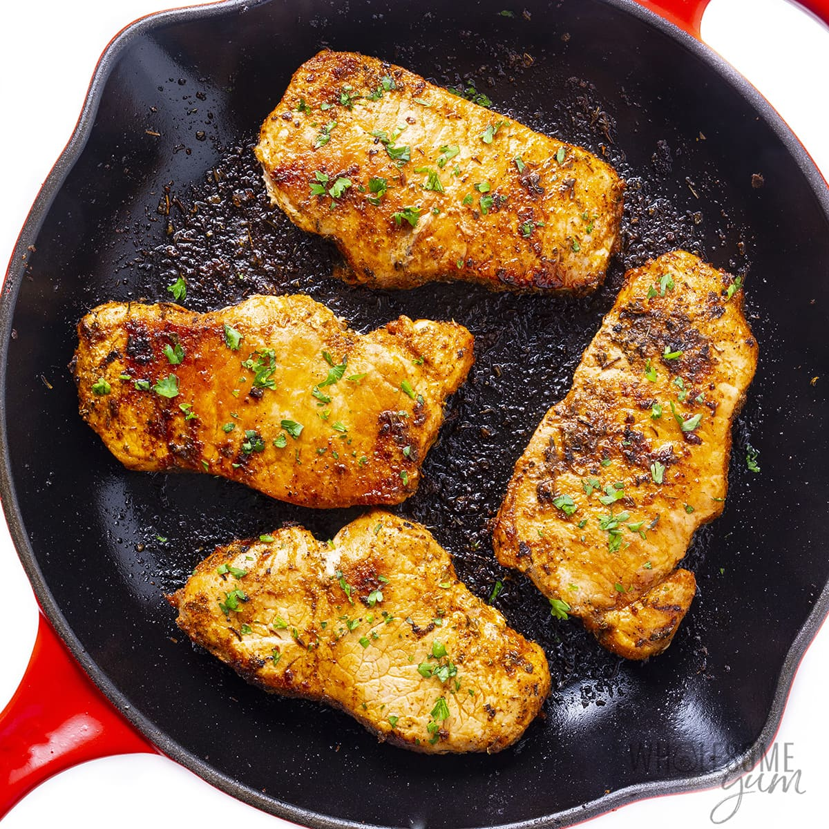 Pork chops in a cast iron skillet cooking