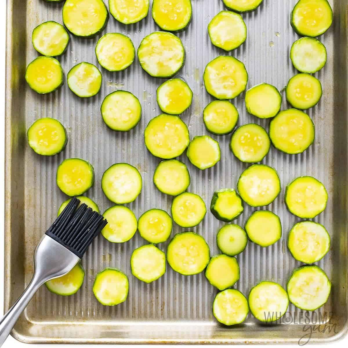 Zucchini slices roasting on a baking sheet