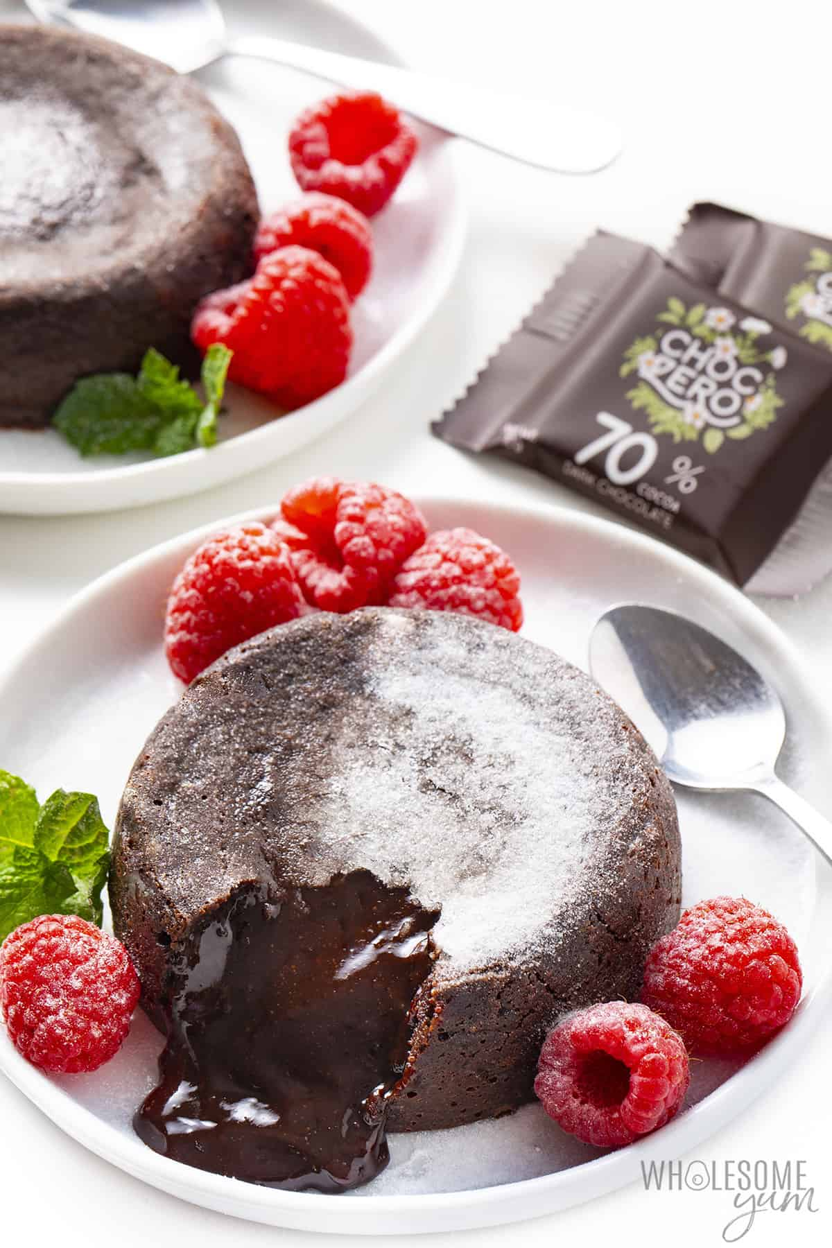 Overflowing keto lava cake on a plate next to ChocZero dark chocolate squares