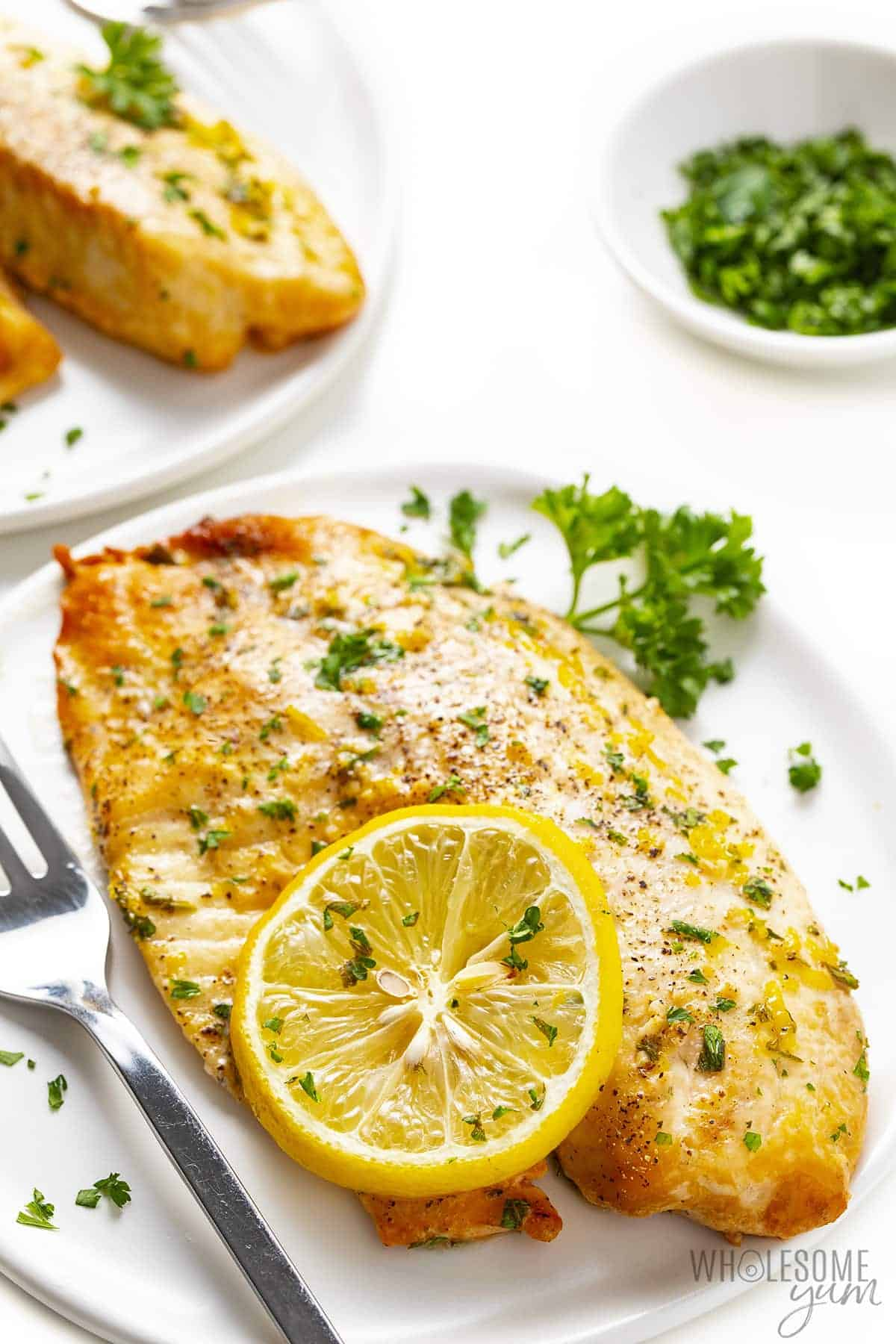 Plate with a piece of lemon butter tilapia