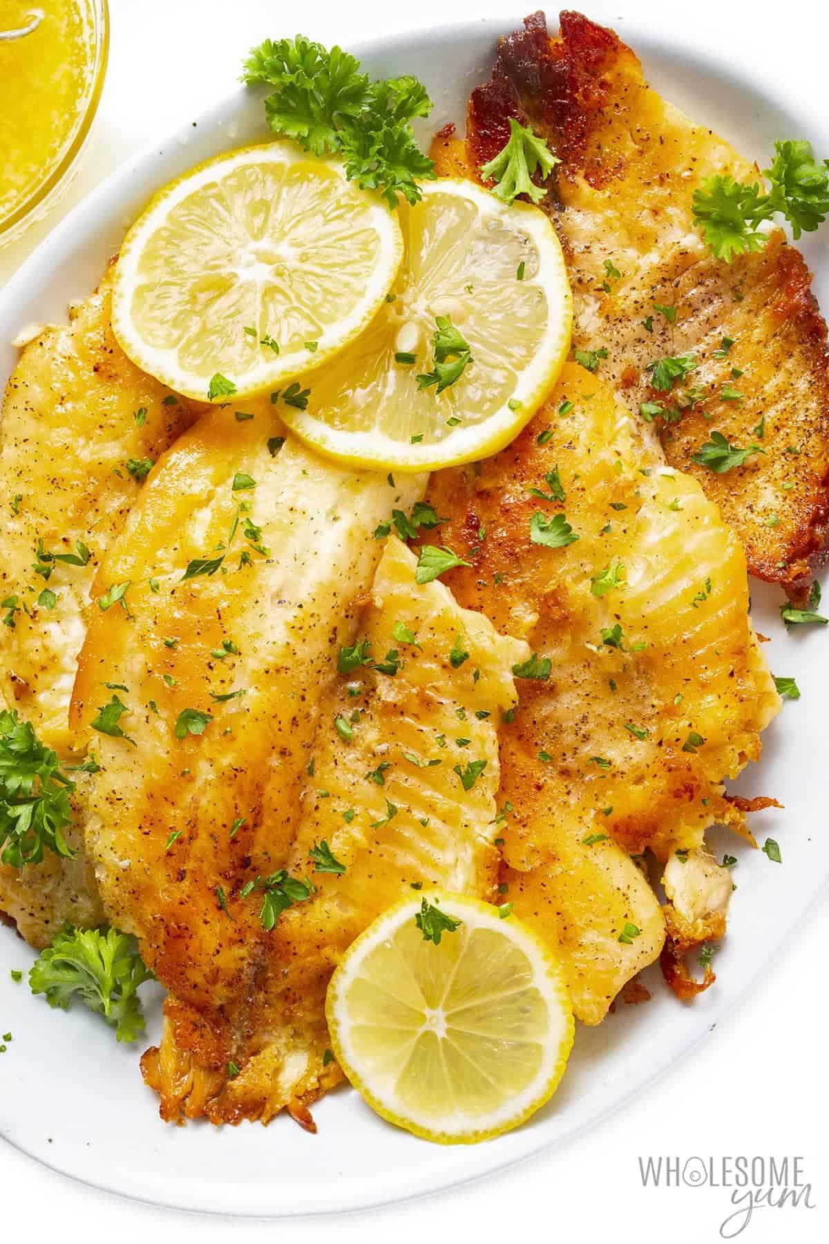 Pan fried tilapia fillets on a platter with lemon slices
