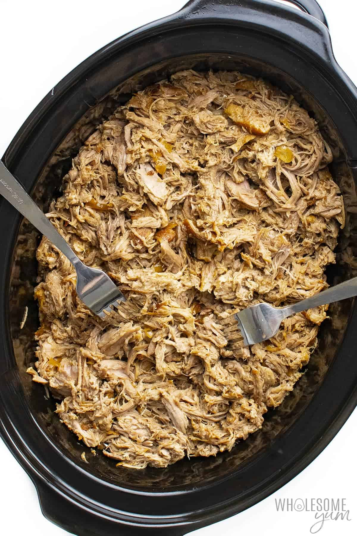 Finished pulled pork recipe in slow cooker with forks